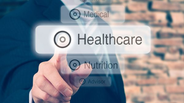 Man in suit pointing at Healthcare graphic