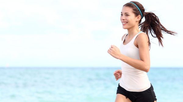 Asian woman running along the beach