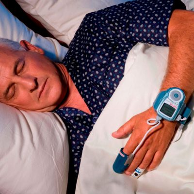 Man sleeping in bed with device attached to finger and wrist