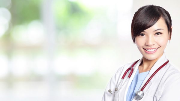 Smiling asian female doctor with arms folded